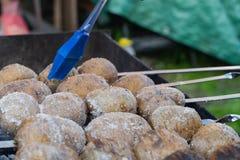 Les pommes de terre cuites au four sur les charbons sur le gril avec une croûte brune gentille ont huilé le gland bleu photos stock