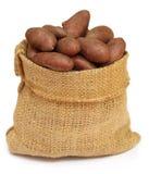 Les pommes de terre dans un sac mettent en sac au-dessus du fond blanc Photo stock
