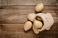 Les pommes de terre fraîches dans le chanvre renvoient des sacs sur le fond en bois rustique Ra Photo stock