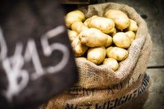 Les pommes de terre fraîches en toile de jute renvoient la vente sur le marché Image stock