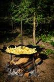 Les pommes de terre frites en huile au-dessus d'un feu en bois, cuit dehors sur le rond peu commun ont courbé le disque d'acier e Image libre de droits