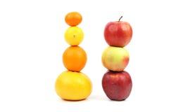 Les pommes et l'agrume se tiennent verticalement sur l'un l'autre sur le backgr blanc Photographie stock libre de droits