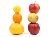Les pommes et l'agrume se tiennent verticalement sur l'un l'autre sur le backgr blanc Photos libres de droits