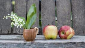 Les pommes et le muguet rouges fleurissent dans une petite tasse en céramique avec le fond en bois Images libres de droits
