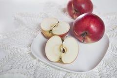 Les pommes et les moitiés rouges des pommes d'un plat sur une serviette de dentelle Image stock