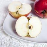 Les pommes et les moitiés rouges des pommes d'un plat sur une serviette de dentelle Images stock