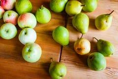 Les pommes et les poires mûres ont dispersé sur la table en bois image stock