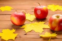 Les pommes fraîches et l'érable jaune part toujours sur la vieille table en bois l Photographie stock