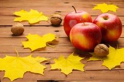 Les pommes fraîches, les noix et l'érable jaune part sur le vieux tabl en bois Image stock