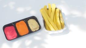 Les pommes frites en aluminium et sauce d'accompagnement 3 sont tomate, piment, sala Photographie stock