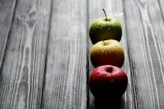Les pommes jaunes vertes rouges dans une rangée avec de l'eau se laisse tomber sur la table en bois noire, lumière arrière Photo libre de droits