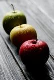 Les pommes jaunes vertes rouges dans une rangée avec de l'eau se laisse tomber sur la table en bois noire, lumière arrière Photos stock