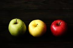 Les pommes jaunes vertes rouges dans une rangée avec de l'eau se laisse tomber sur la table en bois noire, lumière arrière Photo stock
