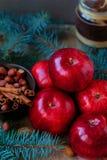 Les pommes rouges pour Noël durcissent avec de la farine nuts et les oeufs en cannelle parent des branches Image libre de droits