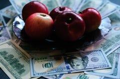 Les pommes rouges sont énumérées sur cent dénominations du dollar Photographie stock libre de droits