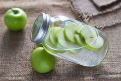 Les pommes vertes fraîches de régime de Detox imbibent dans l'eau du pot sur le sac Photographie stock