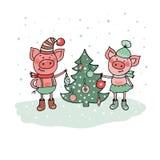 Les porcs drôles s'approchent de l'arbre de Noël Photographie stock