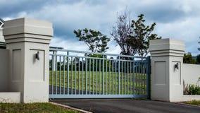 Les portes d'entrée de propriété de résidence privée d'allée en métal ont placé dans la barrière de brique avec des arbres de jar image libre de droits