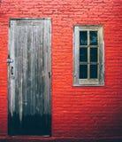 Les portes et la fenêtre donnent au vieux fond une consistance rugueuse rouge de mur Photographie stock libre de droits