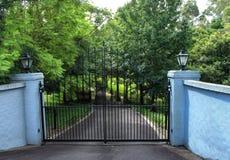Les portes noires d'entrée d'allée en métal ont placé dans la barrière de brique Image libre de droits