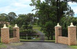 Les portes noires d'entrée de fer travaillé ont placé dans la barrière de brique Image libre de droits