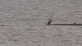 Les postures accroupies d'homme dans le canoë frappe l'eau de lac avec le bâton banque de vidéos