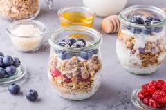 Les pots en verre de l'avoine s'écaille avec le fruit frais, le yaourt et le miel Photo libre de droits