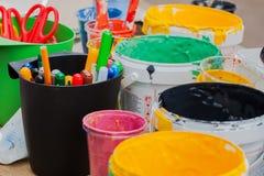 Les pots multicolores avec les peintures, brosse sur la table, marqueurs, colore coloré Image stock