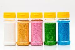 Les pots ont rempli de sucreries colorées utilisées pour des gâteaux, d'isolement sur le blanc Photo stock