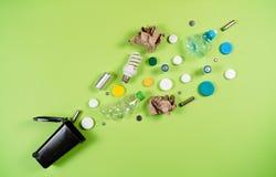 Les poubelles et les déchets assortis d'isolement sur le vert, réutilisent le concept photos stock