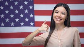 Les pouces- de sourire d'apparence de femme signent sur le fond de drapeau des Etats-Unis, migration clips vidéos