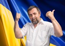 Les pouces lèvent le signe contre le drapeau ukrainien Photographie stock