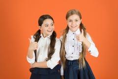 Les pouces se lève pour l'école chic Écoliers avec la mode Peu filles portant l'uniforme à la mode Filles élégantes dans des tres images libres de droits
