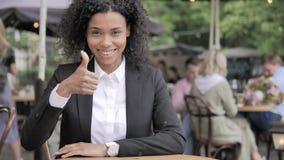 Les pouces se lèvent par la femme d'affaires africaine Sitting en café extérieur banque de vidéos