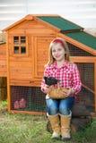 Les poules d'éleveur badinent l'agriculteur de propriétaire d'un ranch de fille avec des poussins dans la cage de poulet Images stock