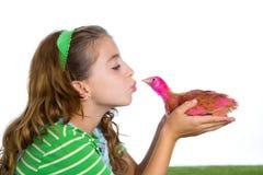 Les poules d'éleveur badinent l'agriculteur de propriétaire d'un ranch de fille embrassant un poussin de poulet image libre de droits