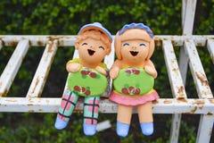 Les poupées d'enfant d'argile tenant le signe embarquent après avoir plu Photographie stock libre de droits