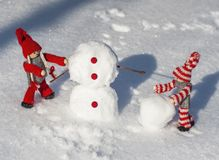 Les poupées en bois en rouge ont tricoté des vêtements roulent vers le bas des boules de neige au buil Image libre de droits