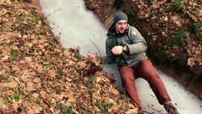 Les pousses d'appareil-photo en tant qu'homme lève qui a glissé sur la glace dans la forêt banque de vidéos