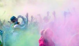 Les pparticipants dans la couleur courent écarter les bras dans le ciel Photographie stock
