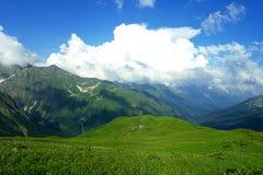 Les prés et les montagnes alpins dans le bleu de brume avec le bel été aménagent en parc Images libres de droits