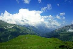Les prés, le lac, les montagnes et les un bon nombr'alpins de nuages blancs avec le bel été aménagent en parc Image stock