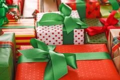 Les présents créatifs élégants en papier coloré décoré du ruban rouge et vert de satin cintre Photos libres de droits