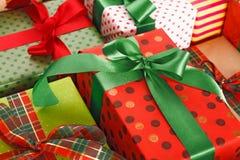 Les présents créatifs élégants en papier coloré décoré du ruban rouge et vert de satin cintre Photo stock
