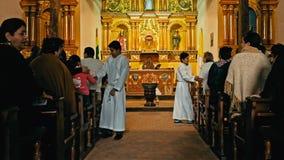 les prêtres marchant parmi les pèlerins à la fin de l'événement de masse de cérémonie serrent la main à chacun dans l'église loca image stock