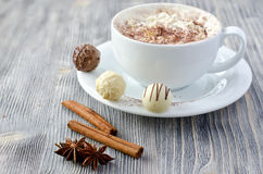 Les pralines et une tasse de cappuccino copient le fond en bois de l'espace Photo stock
