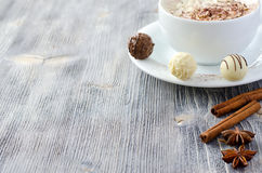Les pralines et une tasse de cappuccino copient le fond en bois de l'espace Images stock