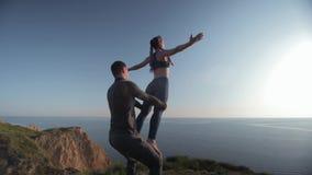 Les pratiques en matière de yoga, fille de sports avec des bras augmentés équilibre sur des jambes de son associé masculin sur le clips vidéos