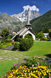 Les Praz de Chamonix and Aiguille Dru mountain. Les Praz de Chamonix medieval church and Aiguille Dru mountain in Alps Stock Photo
