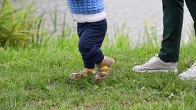 Les premières étapes du bébé garçon, mère suit, mouvement en gros plan et lent banque de vidéos